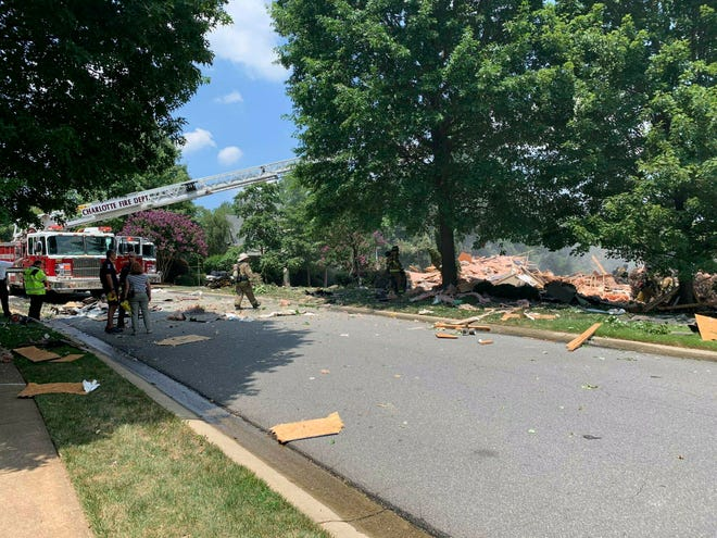 Firefighters look over the wreckage following a fire and explosion at a home in Charlotte on July 2, 2019. Officials say a man who called 911 from the home after the explosion was rescued and taken by helicopter to a hospital with life-threatening injuries.