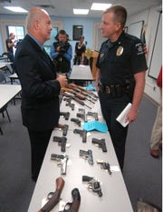 Former Asheville Police Chief Bill Hogan, left, and former Henderson County Sheriff Rick Davis speak over a table of confiscated weapons during a press conference with members of the Western Carolina Gang Task Force in Asheville in 2009.