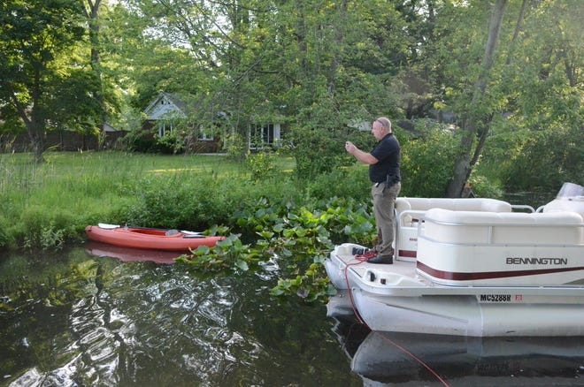 Detective Seth Graves of the Emmett Township Department of Public Safety photographs one of the kayaks recovered Wednesday.