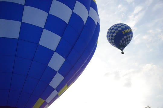 Balloons flown by Phil Clinger, left and Devon Cook, fly Wednesday morning.