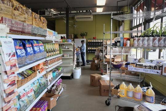 Kitsap Community Food Co-op member and volunteer Bob Dollar puts items on the shelves as the co-op prepares for its grand opening.