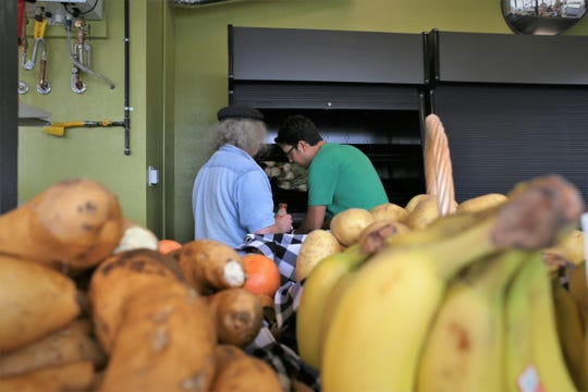Kitsap Co-op board director Manu Alfau, right, and member and volunteer Bob Dollar, left, stock the cold shelves with produce ahead of the new store's grand opening.