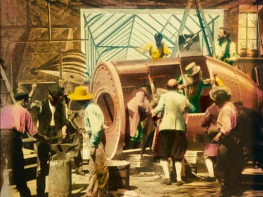 "A colorized still from the 1902 film ""A Trip to the Moon"" shows the space capsule being assembled in a workshop."