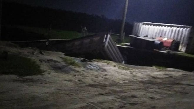 Two massive possible sinkholes swallow numerous semitrailers at an Orange County business.