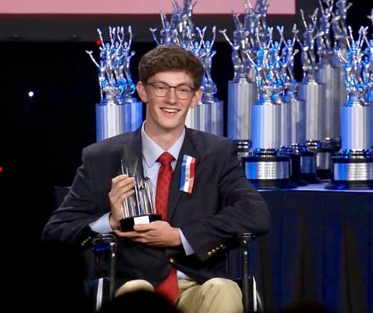 John Henry Stearns receiving his First Place Big Question debate trophy at the National Speech and Debate Tournament in Dallas, TX on June 21, 2019.