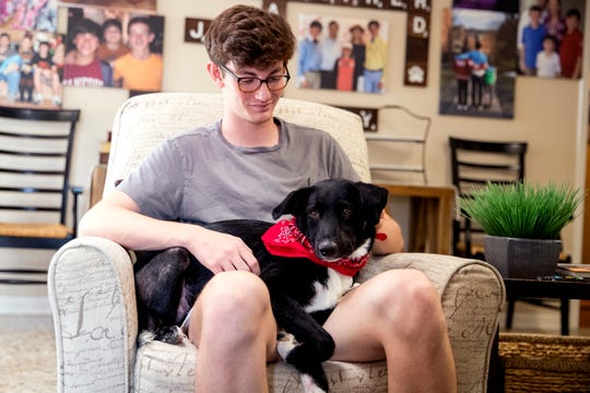 """John Henry Stearns sits with his emotional support dog, Tillman, at his home on Tuesday, July 2, 2019. His dog was named after Tillman Huett-=Lassman, who was a privately paid Lincoln Douglas Debate coach for his first National Tournament in 2013. """"I always thought I'd want a kid named Tillman,"""" he said. """"""""It's a nice reminder of that chapter of my life."""""""