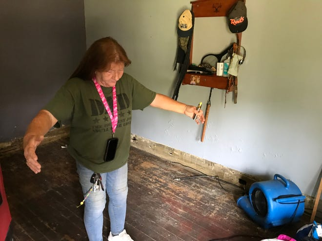 Rosa Collins, 61, of Northside, stands in what was once her bedroom. She demonstrates how rapidly the water rose.