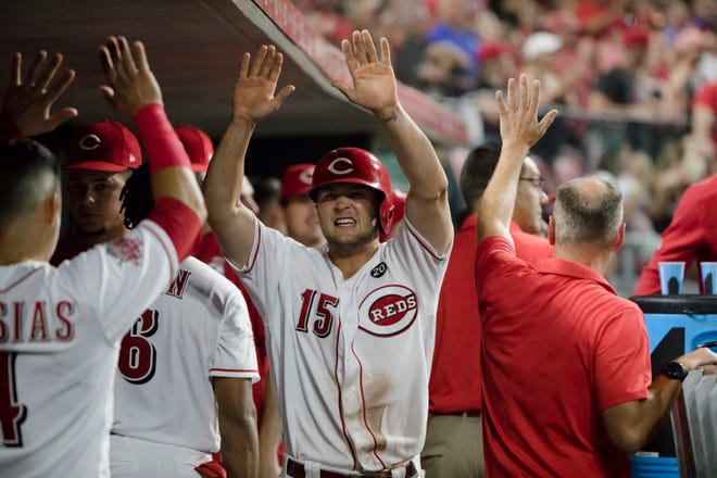 Cincinnati Reds third baseman Nick Senzel (15) celebrates with teammates after scoring the tying run in the eighth inning of the MLB baseball game against Milwaukee Brewers on Tuesday, July, 2, 2019, at Great American Ball Park in Cincinnati. Cincinnati Reds defeated Milwaukee Brewers 5-4 in 11 innings.