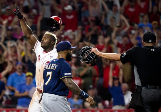 Cincinnati Reds right fielder Yasiel Puig (66) celebrates after scoring the winning run as Milwaukee Brewers first baseman Eric Thames (7) walks by in the bottom of the 11th inning of the MLB baseball game on Tuesday, July, 2, 2019, at Great American Ball Park in Cincinnati. Cincinnati Reds defeated Milwaukee Brewers 5-4.