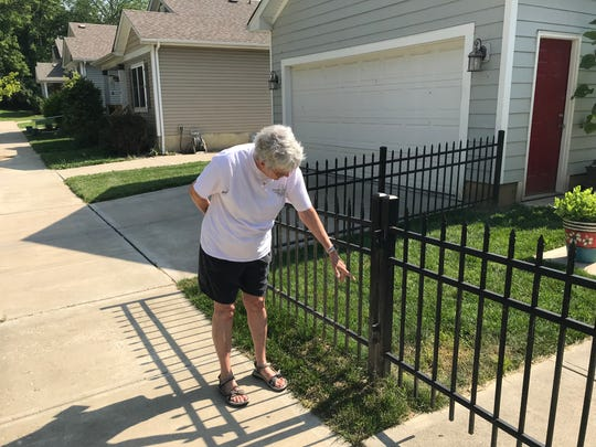 Sandi Kelly shows how high the water rose outside her Northside home on Martha Street.