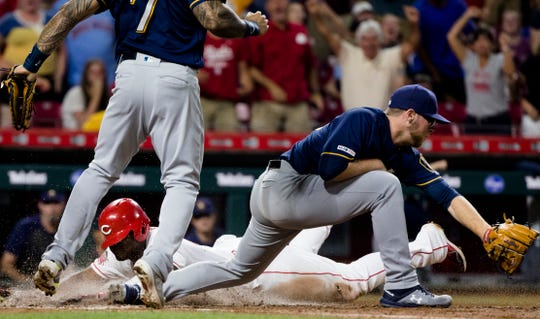 Cincinnati Reds right fielder Yasiel Puig (66) dives into home for the winning run as Milwaukee Brewers starting pitcher Corbin Burnes (39) attempts to tag him out in the bottom of the 11th inning of the MLB baseball on Tuesday, July, 2, 2019, at Great American Ball Park in Cincinnati. Cincinnati Reds defeated Milwaukee Brewers 5-4.