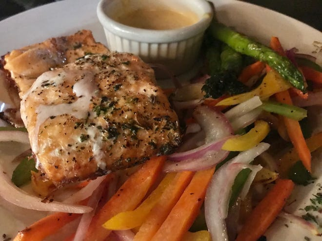 The Cosi Wood Fired Salmon features an 8-ounce filet with Julienned vegetables, asparagus and a creamy dill sauce at the Cosi Cucina Italian Grill in Clive.