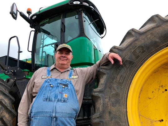 In this Thursday, June 20, 2019, photo, farmer Bernard Peterson leans on a tractor at his farm in Loretto, Ky. When the Trump administration announced a $12 billion aid package for farmers struggling under the financial strain of his trade dispute with China, the payments were capped, but many large farming operations found legal ways around the limits. (AP Photo/Dylan Lovan)
