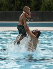 Counsel Gaynor of Detroit tosses his son Counsel Gaynor Jr 4 while on Wednesday July 9, 2014 after the grand re-opening of the two olympic-size swimming pools and bath house at the historic Brennan Pools located in Rouge Park on Detroit's west side. Ryan Garza / Detroit Free Press