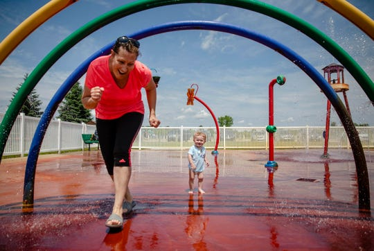 Weather across Michigan Tuesday included hot temperatures, bright sunshine and storms. In Grand Blanc, 13-month-old Emmett Bowers plays at a splash pad with his grandmother Suzan Scott on Tuesday, July 2, 2019. Sunshine, hot temperatures and a threat of storms are forecast through the weekend.