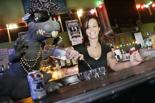 Bartender Dana Dunwoodie of Dearborn Heights pours shots in 2008 under the watchful eye of Merlot, the Lager House's rubber rodent mascot.