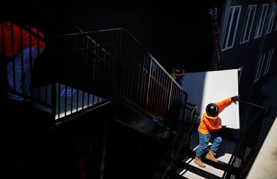 Construction workers carry material down a staircase while working on a new mixed-use development featuring apartments and retail space along the BeltLine, a former railroad corridor converted into parks and trails, in Atlanta.