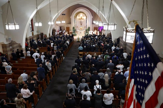 Mourners stand during the funeral Mass for Detective Luis Alvarez.