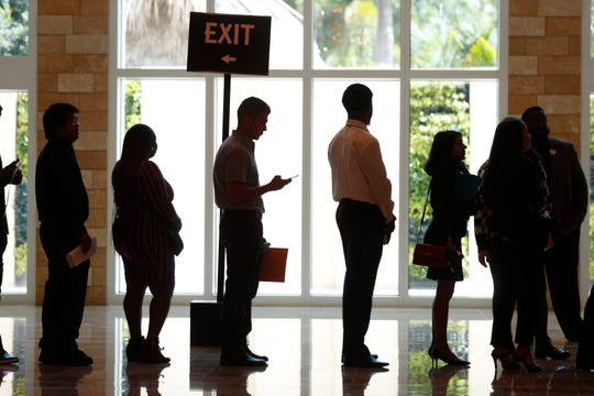 Job applicants line up at the Seminole Hard Rock Hotel & Casino Hollywood during a job fair in Hollywood, Fla.