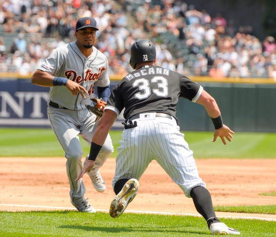 The Chicago White Sox's James McCann gets caught after overrunning third base before being tagged out by Detroit Tigers third baseman Jeimer Candelario.