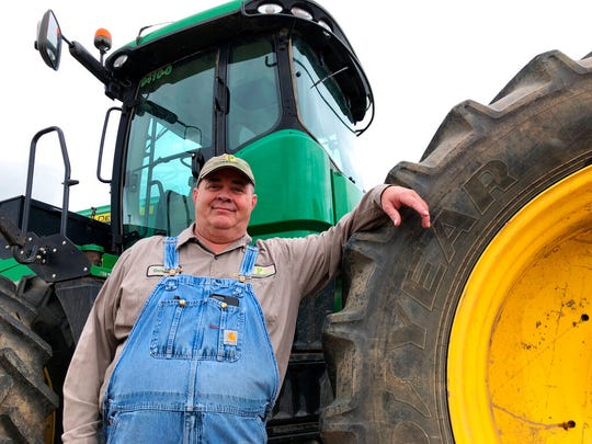 In this Thursday, June 20, 2019, photo, farmer Bernard Peterson leans on a tractor at his farm in Loretto, Ky. When the Trump administration announced a $12 billion aid package for farmers struggling under the financial strain of his trade dispute with China, the payments were capped. But records obtained by The Associated Press under the Freedom of Information Act show that many large farming operations easily found legal ways around the limits to collect big checks.