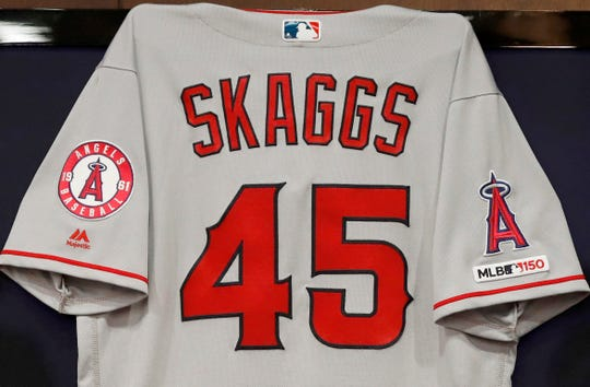 The jersey of the late Tyler Skaggs hangs on the wall during a news conference with team management and ownership.