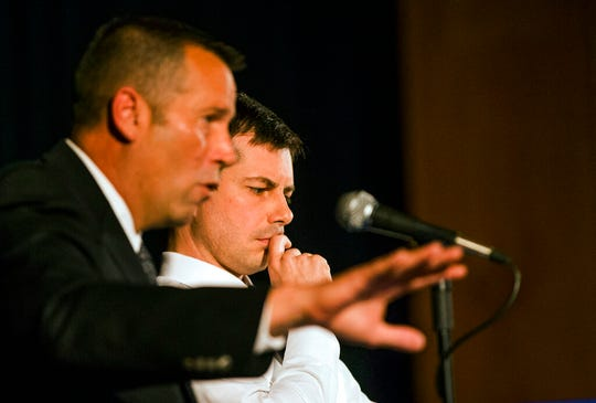 "In this June 23, 2019 file photo, South Bend Police Chief Scott Ruszkowski, left, speaks as Democratic presidential candidate and South Bend Mayor Pete Buttigieg listens during a town hall community meeting, in South Bend, Ind. A white police officer who fatally shot a black man in the Indiana city where Buttigieg is mayor says he and his family never expected to be ""thrown into the middle of a Presidential campaign."" Eric Logan's fatal shooting by South Bend Sgt. Ryan O'Neill forced Buttigieg, who's seeking the Democratic presidential nomination, off the campaign trail for days."