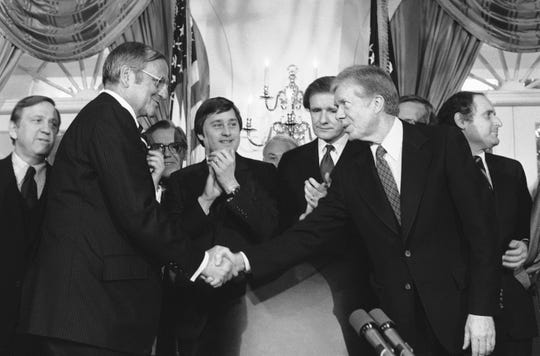 U.S. President Carter leans over to shake hands with Chrysler Chairman Lee Iacocca during signing ceremonies in the Cabinet room of the White House, Washington, Monday, Jan. 8, 1980 for legislation guaranteeing the Chrysler loan.