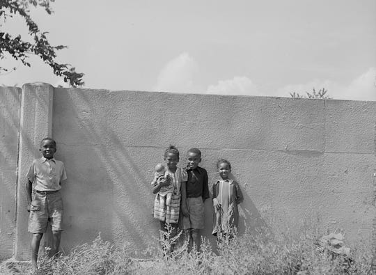 Children stand in front of the half mile concrete wall in Detroit shortly after it was erected in 1941 to separate the black residents from a white housing development going up on the other side.