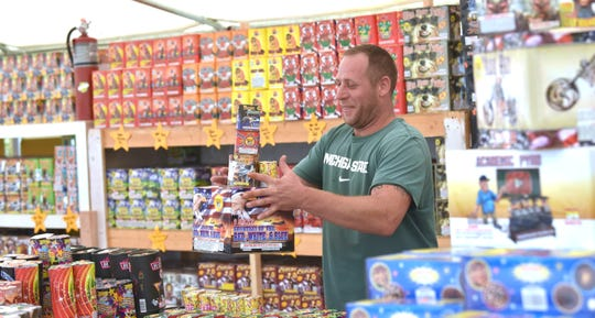Customer Dominick Aleardi, of Chesterfield Twp., prepares to pay for his stack of fireworks at Global Dreams, Inc., which has a tent set up in the parking lot of the Chesterfield Market shopping center at Gratiot and Carriage Way in Chesterfield Twp., Wednesday morning.