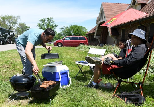 From right, Ed Natavio, 46, of Lake Orion and his son, Ethan Natavio, 12, relax while Ed's brother, John Natavio, 47, of Detroit tends to the meat on the grill on Belle Isle in Detroit on Memorial Day.