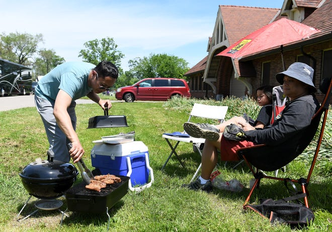 Ed Natavio, right, of Lake Orion and his son, Ethan Natavio, 12, relax while Ed's brother, John Natavio of Detroit tends to the meat on the grill on Belle Isle in Detroit on Memorial Day 2019.