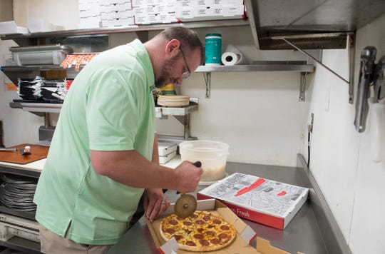 Matthew Klees cuts a pizza in the kitchen at Kipplee's Wednesday, July 3, 2019.