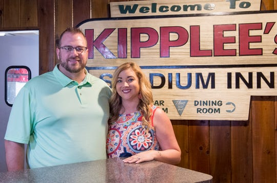 Matthew and Kaycey Klees pose in front of the old Kipplee's Stadium Inn sign in the lobby of Kipplee's Wednesday, July 3, 2019. The Klees took ownership of the longtime Evansville restaurant on July 1.