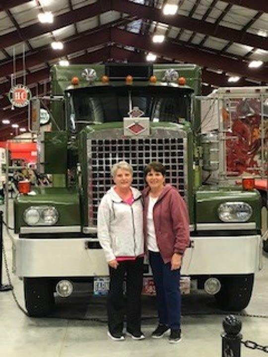 Sisters Kathy Green, left, and Marie Green stand in front of their father's 1974 Diamond Reo semi at the Iowa 80 Trucking Museum.