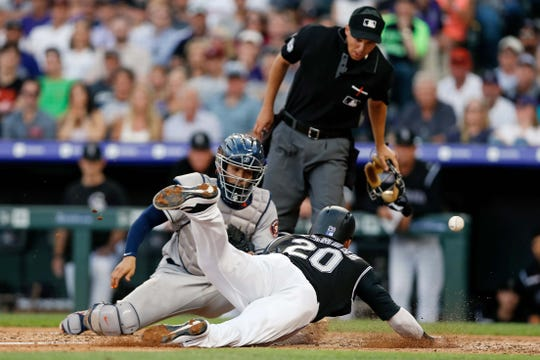 Colorado Rockies outfielder Ian Desmond dives safely into home plate as the ball gets away from Houston Astros catcher Robinson Chirinos during a game Tuesday at Coors Field in Denver. The Rockies begin a three-game series at Arizona at 7:10 p.m. Friday.