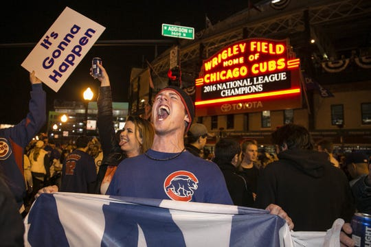 """A Chicago Cubs fan hold a """"W"""" flag as he celebrates outside  Wrigley Field after the Cubs won the National League pennant in 2016."""