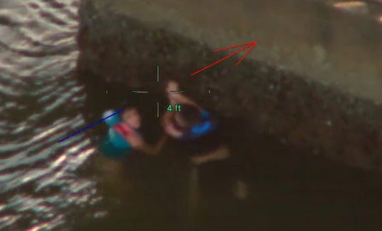 Two juveniles cling to a bridge support pillar under the Sanibel Bridge after they fell off a Jet Ski and were swept under the span Tuesday night. The two were rescued by the Lee County Sheriff's Office.
