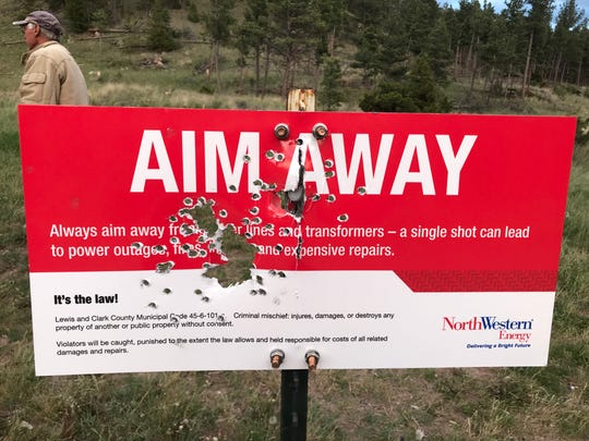 A sign asking people to shoot away from utility poles was vandalized within a few days.