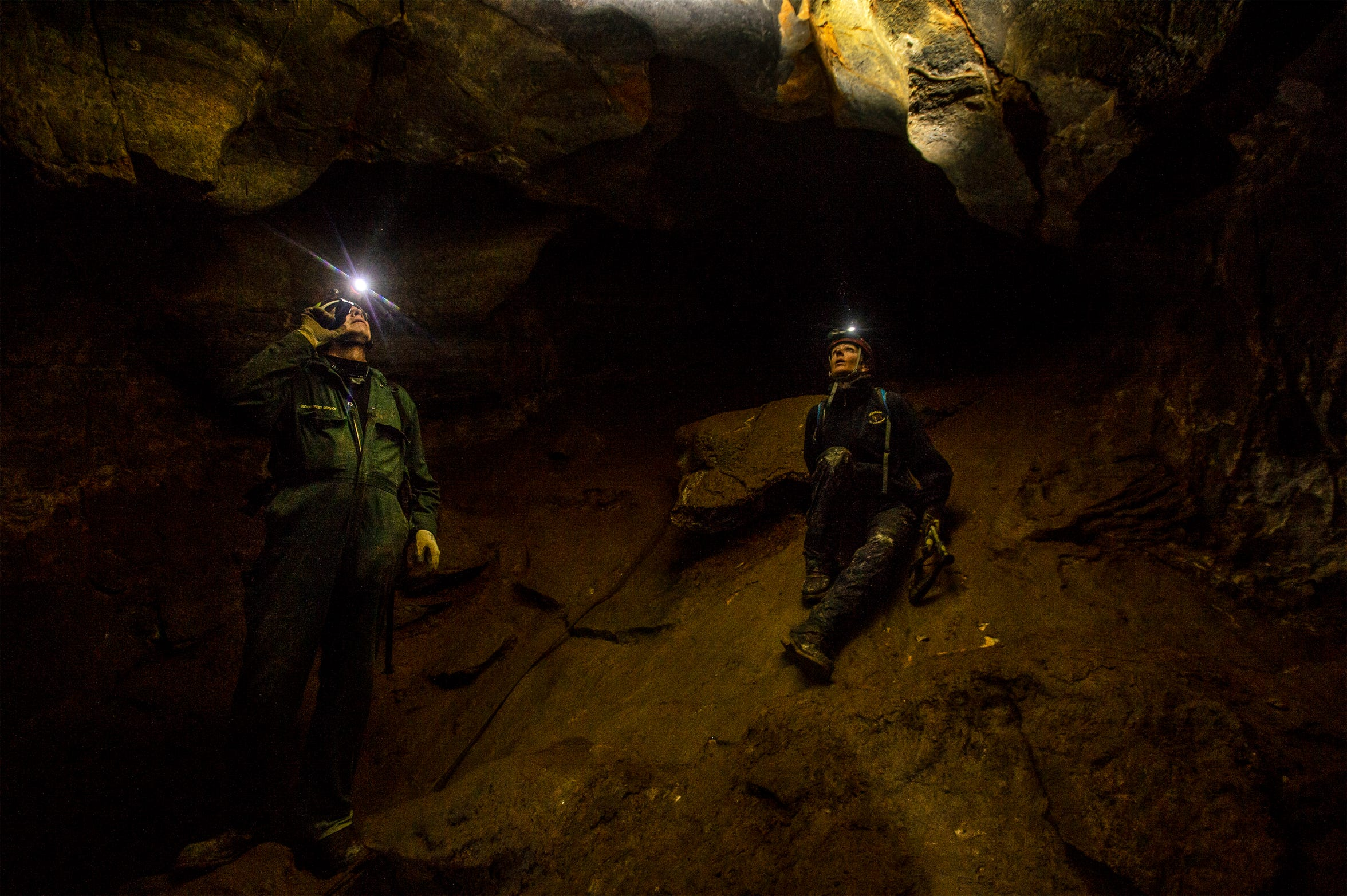 Dave Bobbitt, left, geologist with the U.S. Forest Service, and Lauri Hanauska-Brown, Non-game Wildlife Management Bureau chief for Montana Fish, Wildlife & Parks, search the walls of Lick Creek Cave in the Helena-Lewis and Clark National Forest for bats they can test for   white-nose syndrome.  The syndrome is caused by a fungus, Pseudogymnoascus destructans, which has yet to be detected in Montana but has killed millions of bats in the eastern United States and Canada.
