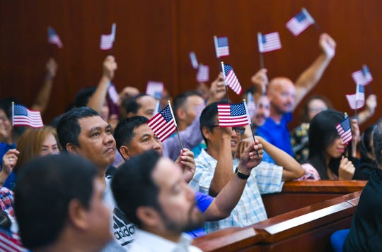 Families, friends and other supporters of new citizens wave miniature American flags during a special naturalization ceremony at the District Court of Guam in Anigua on Wednesday, July 3, 2019. The ceremony, held in celebration of Indepedence Day, welcomed 43 new citizens originally from the countries of China, India, Japan, Peru, the Philippines, South Korea and Taiwan.