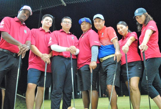 """In this file photo from July 2019, Guam's representatives to the Pacific Games in Samoa take time for a photo during a team practice at the Tumon Driving Range. Pictured from left are team captain Daryl Poe, Ricardo Terlaje, Eduardo """"Pollo"""" Terlaje, John-Anthony Muna, Robert Manalo, Emeri Satake and Rose Tarpley. Not pictured is Kristin Oberiano."""