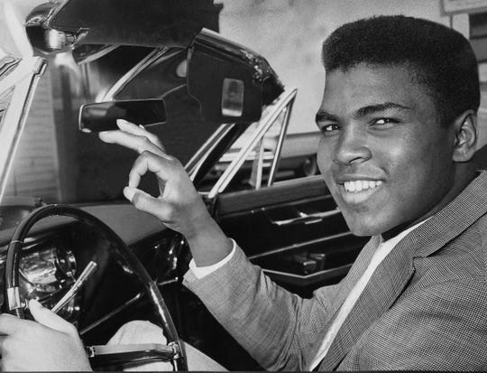Ali gives a victory sign as he poses behind the wheel of his 1963 convertible after getting his driver's license on March 29, 1963.