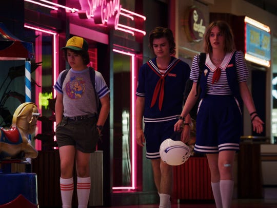"""Stranger Things"" characters Dustin, left, Steve and Robin walk by a Sam Goody record store at Starcourt mall in fictional Hawkins, Indiana. Steve and Robin work at a Scoops Ahoy ice cream parlor in the new season of the Netflix series."