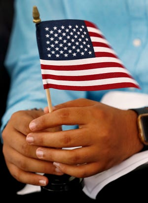 New citizen Kerolos Fahmy holds an American flag during a naturalization ceremony at the Benjamin Harrison Presidential Site, Wednesday, July 3, 2019.  Each new citizen received the small flags when their country of origin was called.  31 countries were represented at this ceremony.  Fahmy is from Greece.