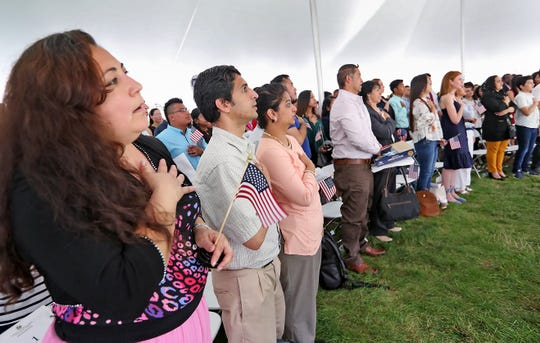 New citizens say the Pledge of Allegiance during a naturalization ceremony at the Benjamin Harrison Presidential Site, Wednesday, July 3, 2019.