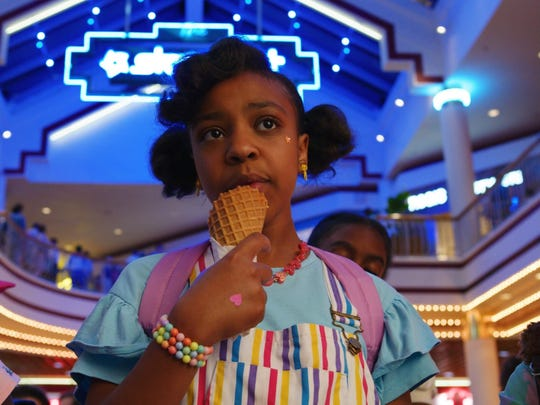 "Erica Sinclair enjoys an ice cream treat at Starcourt Mall in an episode of ""Stranger Things 3."""