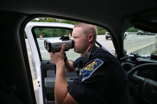 Indiana State Police Trooper Andrew Forgey sits alongside I-65 on Indianapolis' Southside in an unmarked INDOT Ford 150 pickup truck as he looks for speeders in the construction zone on Friday, August 29, 2014.