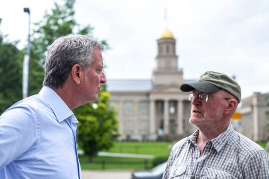 Democratic presidential candidate Bill de Blasio, Mayor of New York City, talks with Jim Throgmorton, Mayor of Iowa City, Wednesday, July 3, 2019, along Clinton Street across from the Old Capitol building in downtown Iowa City, Iowa.