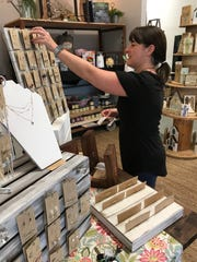 Tina Loftin of Florence replenishes the stock of earrings and necklaces she sells at Cotton & Tumbleweeds.